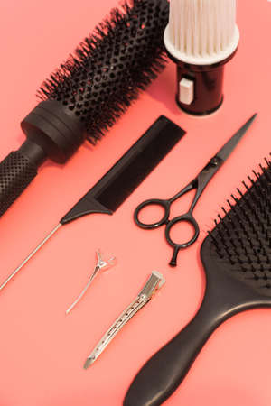 Flat lay composition with hairdresser set on pink background. Barber set with tools and equipment: scissors, combs and hairclips. Hairdresser and beauty salon service.