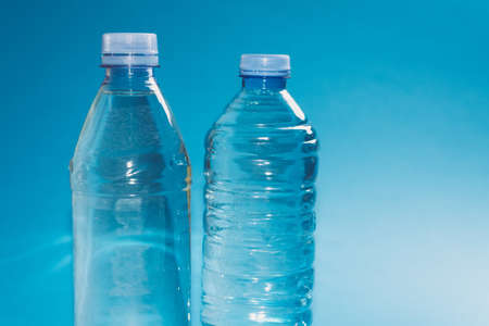 Two different plastic bottles with a sparkle of water on a blue background. Copyspace, place for text. Stock Photo