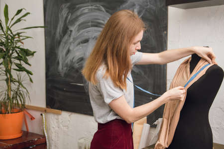 Seamstress tries on fabric on a black mannequin in a sewing workshop. The designer designs a dress from beige fabric and creates clothes. female dressmaker attach fabric to mannequin with needles. creating dress design. Tailor industry concept.