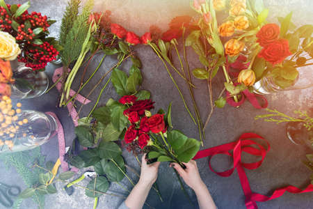 A beautiful girl collects a dark bouquet of burgundy red roses in her studio. Flat lay, top view. Flowers delivery, creating order, Small business. Stock Photo