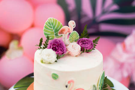 Pink cake with flamingos for the holiday. Cake with a variety of decorations, palm leaves and fresh flowers.
