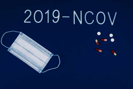 the word 2019-ncov laid with white letters on classic blue background with dramatic light. Novel coronavirus disease named 2019-nCoV . Pills and breathing mask as a concept of coronavirus. Stockfoto