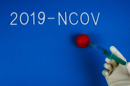 A doctor in a plastic white glove injects a syringe into a red ball of coronavirus. Treating infection. The word 2019- ncov on a blue background. Flat lay.