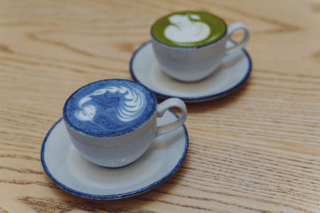 Blue and green matcha in ceramic white mugs on a wooden table with copyspace.