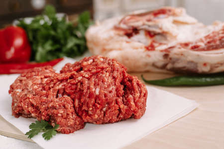 Red fresh minced meat on the background of lamb legs, red pepper and greens. Ground beef on the background of fresh meat in the kitchen of a housewife. 스톡 콘텐츠