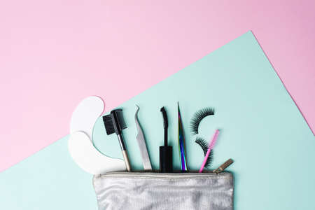 Silver cosmetic bag with a set for eyelash extension and dyeing. Eyelash extension tweezers, false eyelashes, eye patches and eyebrow brush on a trendy pastel background.