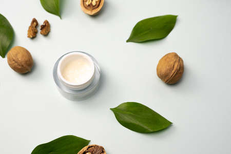 Yellow cream made from natural ingredients on a blue pastel background with green leaves and walnuts. The concept of creating essences from natural ingredients.