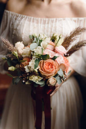 Delicate, stylish bouquet of roses, peonies in the hands of the bride in a wedding dress. Vertical beautiful wedding concept.