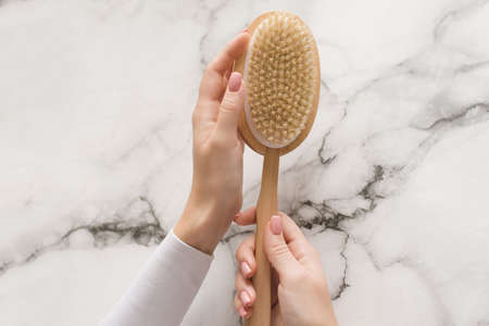 Brush for dry massage in the hands of a girl on a marble background. Brush for scrubbing the body, bringing it in order, against cellulite and orange peel.