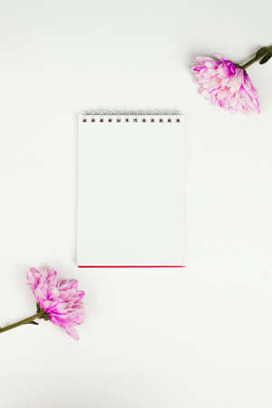 Blank notebook with pink flower on a white background. Top view of little plant with flowers on blank notebook on white fabric workspace background. Copyspace, mockup.