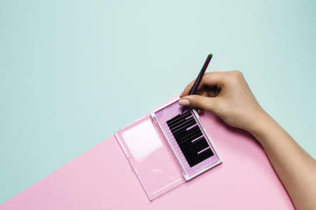 Girl holds tweezers over a pink box with black eyelashes on a pastel background. Woman's hand takes artificial eyelashes for extension. Eyelash extension concept.