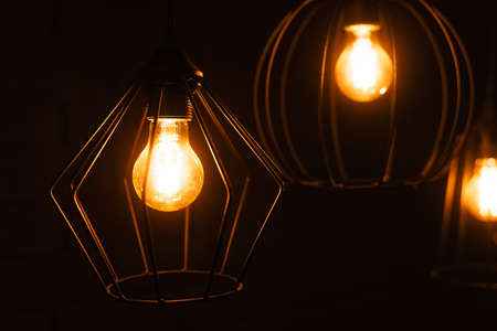 Close-up of an incandescent lamp. Light bulb with orange light. Burning an incandescent edison lamp with a large decorative spiral.