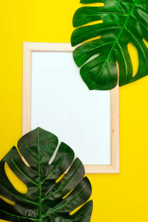 Top view of a white square frame mockup with palm leaf decoration. Summer composition on yellow background.