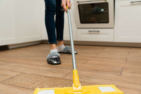A woman washes underfloor heating in her house. A mop in the hands of a housekeeper. Imagens