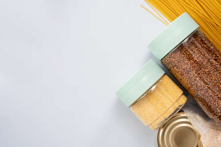Porridge, buckwheat, canned food, tea and essentials on a blue background with place for text. Template for designer.