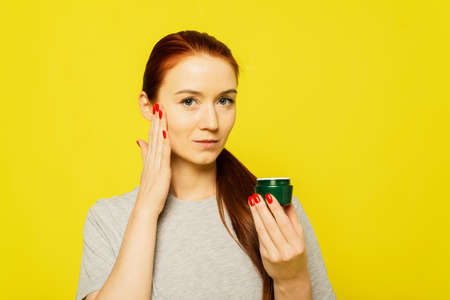 A red head girl is applying cream on the face . A girl smears face cream on the yellow background. 写真素材