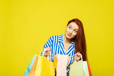 Beautiful woman on a yellow background looks in bags with clothes and different purchases after shopping and is surprised.