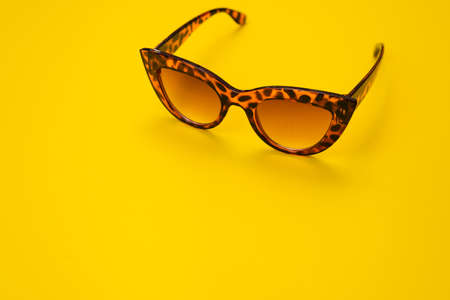 Stylish brown sunglasses on yellow background with copy space.
