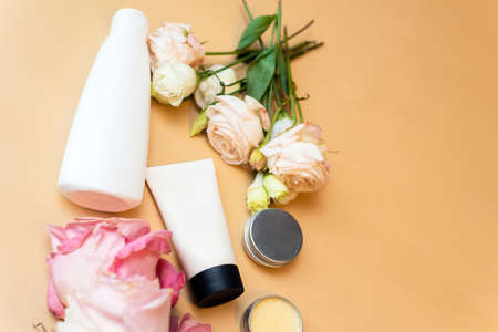 Cream and lotion in white tubes on a beige background with flowers of roses. Cosmetic products for skin care from natural ingredients.