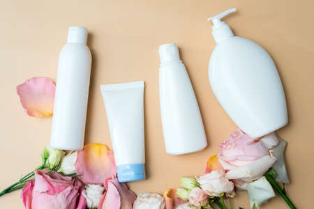 Cosmetics from natural ingredients and extracts of flowers and roses on a beige background. Cream, lotion, gel in white tubes with mock up.