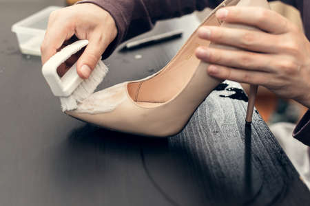 Leather shoes care concept. Shoe cleaning and polishing. Close up picture of woman hands cleaning shoes.