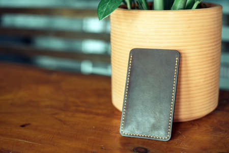 The black phone case made of eco-leather is made by a master. Handmade phone case on a wooden background against a plant.