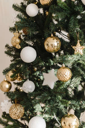 Gold and white Christmas ball on a Christmas tree in a light interior against the background of burning garlands of lights. Decorating Christmas tree on bright background.
