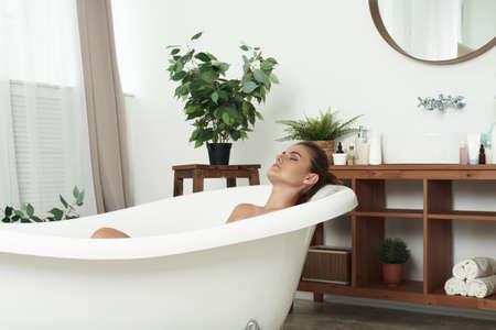 Beautiful woman relaxing in a bath tub with her eyes closed in bliss and pleasure profile view. Young woman relaxing in the beautiful bath in the retro bathroom. Standard-Bild