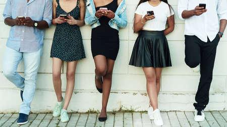 Group of friends watching smart mobile phones. Group of multicultural friends using smartphone outdoors. Zdjęcie Seryjne