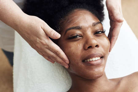 Smiling black woman enjoying a toning facial massage. Serene woman relaxing outdoor in a beauty center.