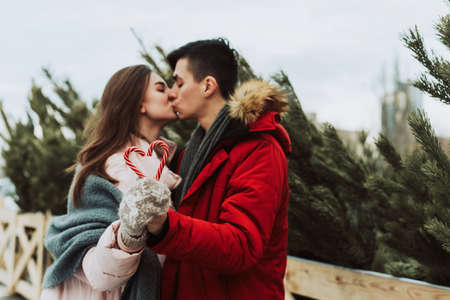 A young woman and a man hold heart-shaped caramel canes and kiss against the backdrop of the Christmas tree bazaar in the city.