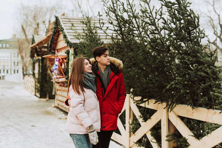A lovely, young couple is having fun choosing a Christmas tree for home at the Christmas tree market. Concept for love, New Year, Christmas and shopping for gifts. Stockfoto