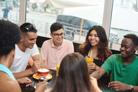 Multiracial happy young people drink coffee at cafe, black and white cheerful mates laughing enjoying drinks having fun sitting together at restaurant table, diverse friends share lunch at meeting.