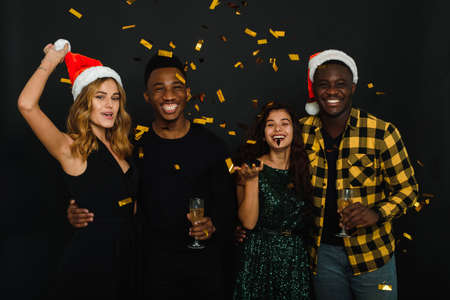 Four friends of different nationalities throw confetti in santa claus hats and antlers and drink champagne against a black background. A company of young people celebrates Christmas and New Year.
