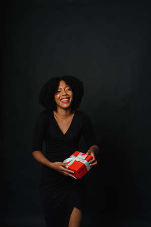 A dark-skinned woman with an afro hairstyle gives a gift to the camera. The concept of New Years shopping, gifts. Copy space.
