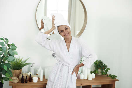 A smiling young woman has just come out of the shower and is standing in the bathroom. Skin care, morning routine.