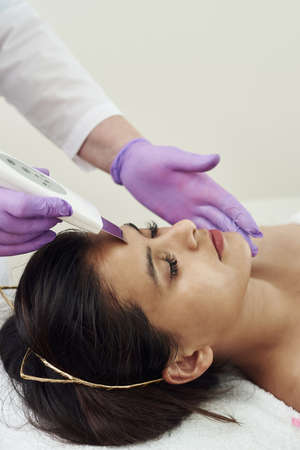 Doctor with Ultrasonic scraber. Young woman receiving cleansing therapy with a professional ultrasonic equipment in cosmetology office