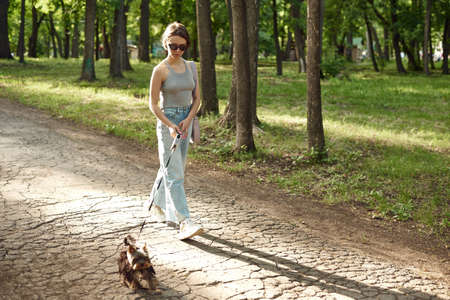 Active young woman with a dog for a walk in a beautiful summer nature. Outdoor