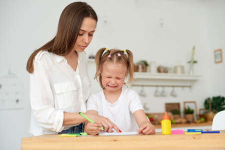 Kind mother embracing and comforting small crying daughter having difficulties with homework while sitting at table and doing exercise in copybook in kitchen. Help with homework Foto de archivo