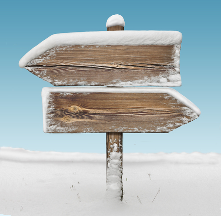 Wooden direction sign with snow on it and with sky on background. two arrows in opposite directions