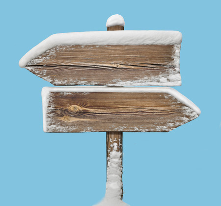 Wooden direction sign with snow on it isolated on blue. two arrows in opposite directions Stock Photo