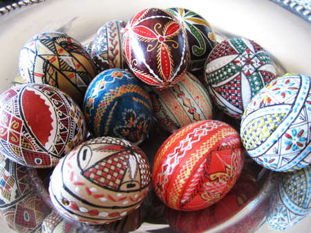 romanian: Close-up view of a silver bowl with many Romanian decorative eggs
