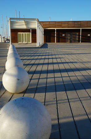 Urban esplanade with spherical benches and a wooden building in a sunny day photo