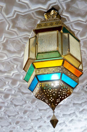 Arabic colorful lantern hanging from a white decorated ceiling photo