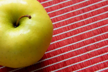Close-up view of a golden apple on a red tablecloth photo