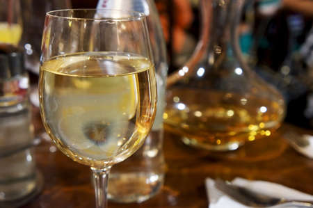 Close-up view of a glass of white wine on a wooden table                                photo