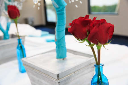 wedding reception decoration: blue vase and red flower on a table