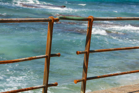 beach closed: Rusty fence in the sea