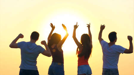 group of happy young people dancing on beautiful sunset
