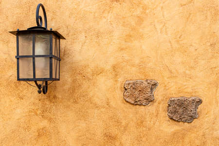 Rustic wall, orange and yellow textures with embed stone and iron light